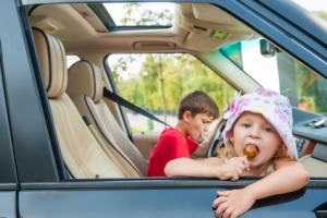 Two kids is going by car without parents. Girl eats candy, boy d